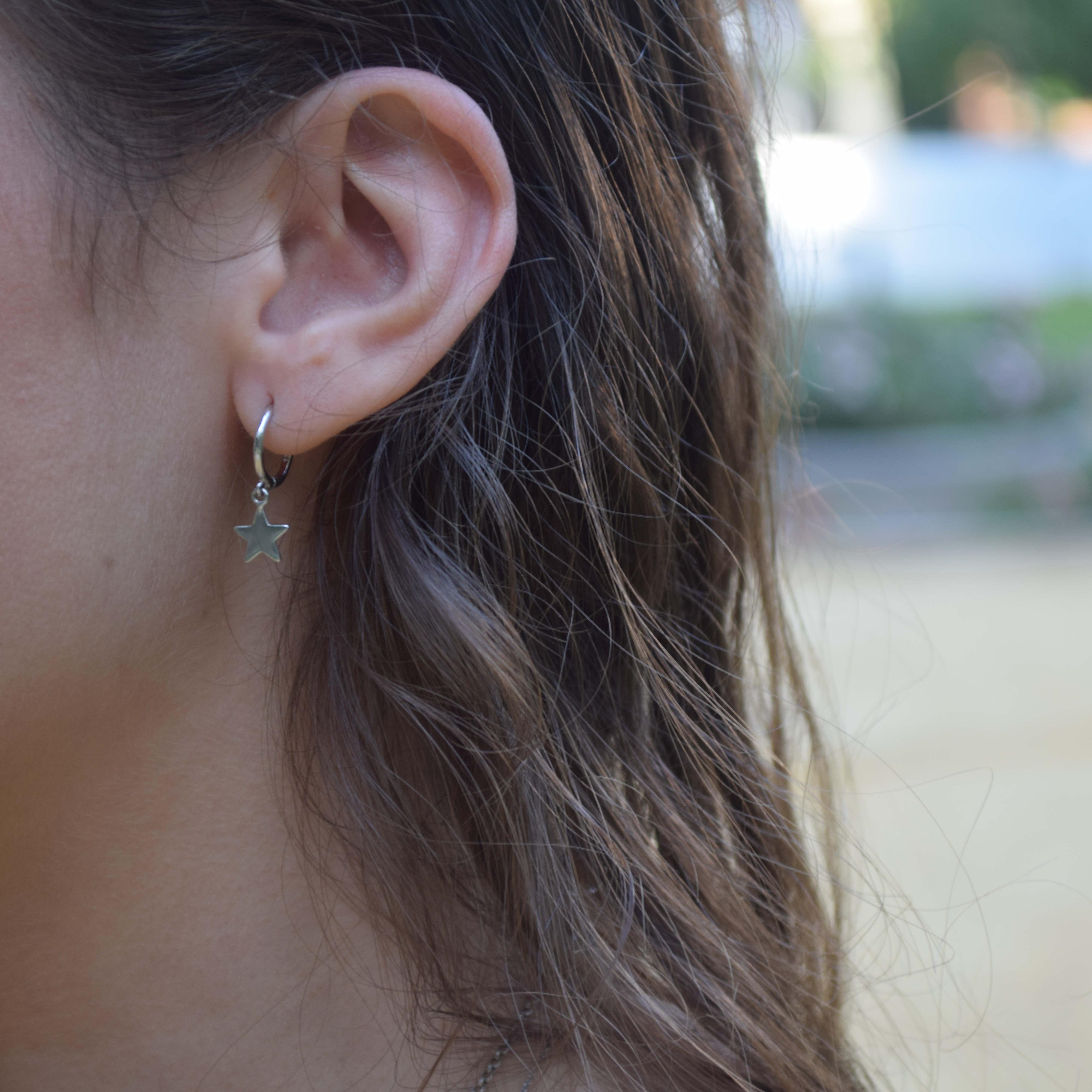 aros estrella plata puestos en oreja